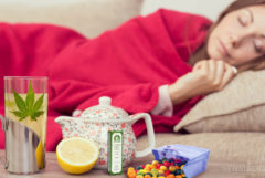 A woman lying on the sofa with a blanket. On the table are different cold treatments
