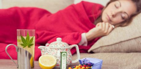 Una mujer tumbada en el sofá con una manta. En la mesa hay diferentes tratamientos fríos.