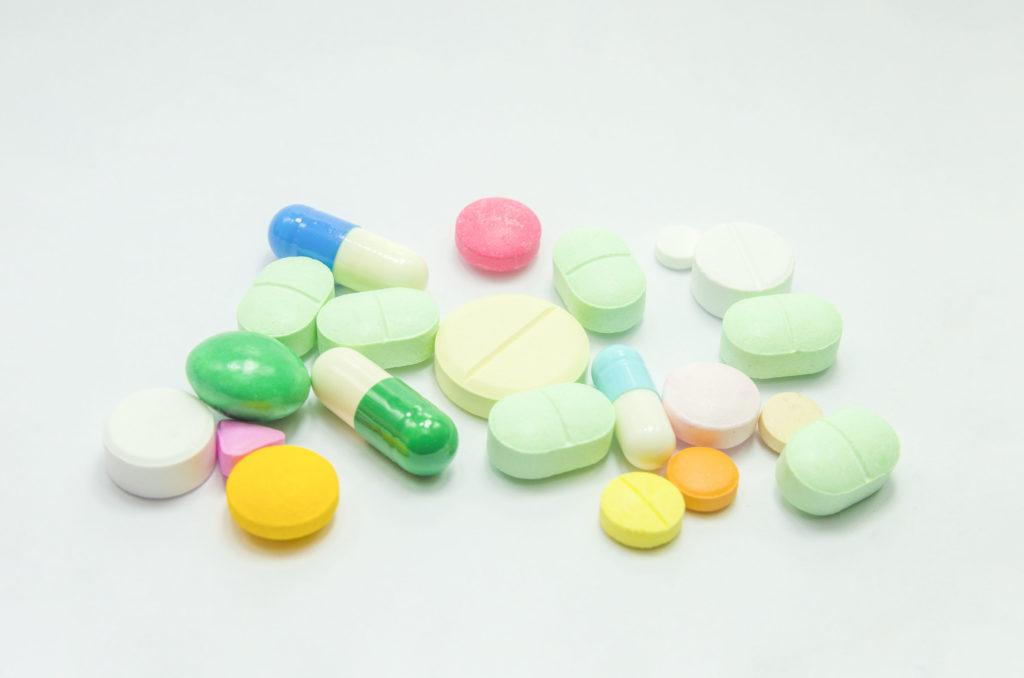 Einundzwanzig farbige medizinische Pillen aller verschiedenen Formen und Größen, die auf einer leeren Oberfläche verstreut sind