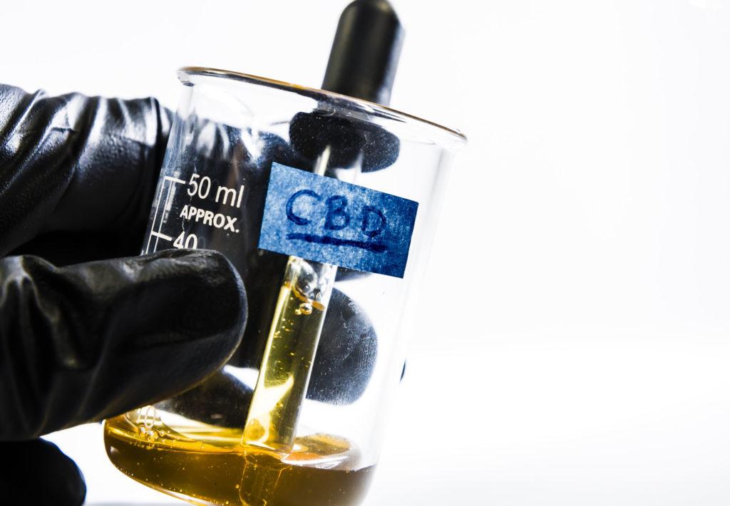 Eine Spritze in einem Glasgefäß voller brauner Flüssigkeit mit cbd