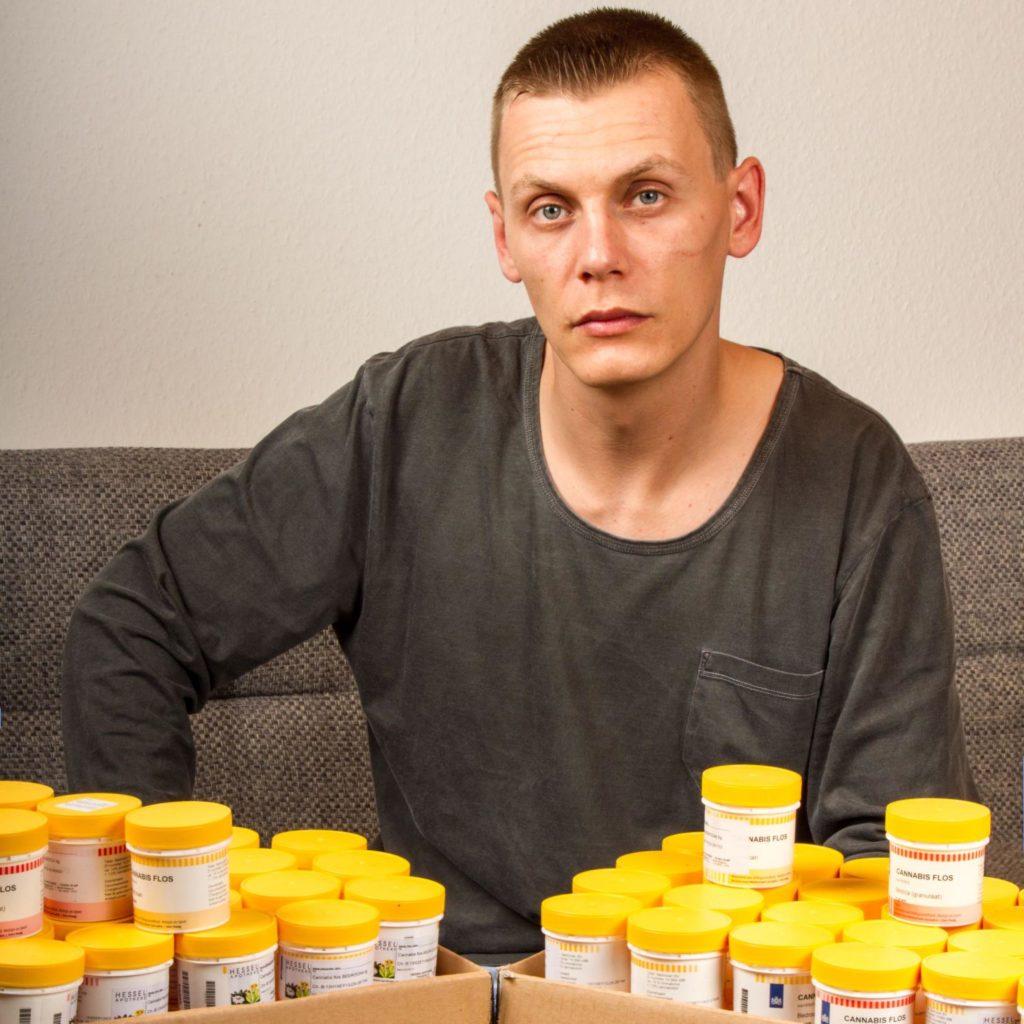 Alexander Jähn assis sur un canapé avec des conteneurs médicaux devant lui