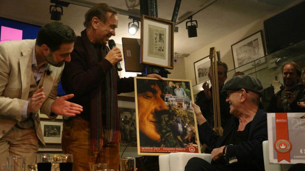 Trois hommes en regardant une affiche sur scène aux récompenses de la culture du cannabis