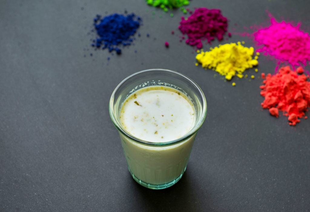 A small glass full of white liquid and piles of different coloured powders