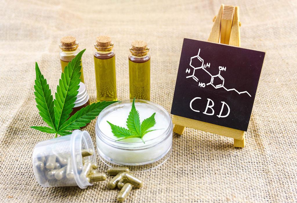 The chemical formula of CBD on a mini chalkboard, CBD oil, capsules, and cream