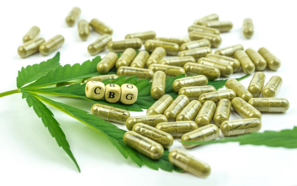 Una hoja de cannabis y un puñado de cápsulas de píldora marrón.