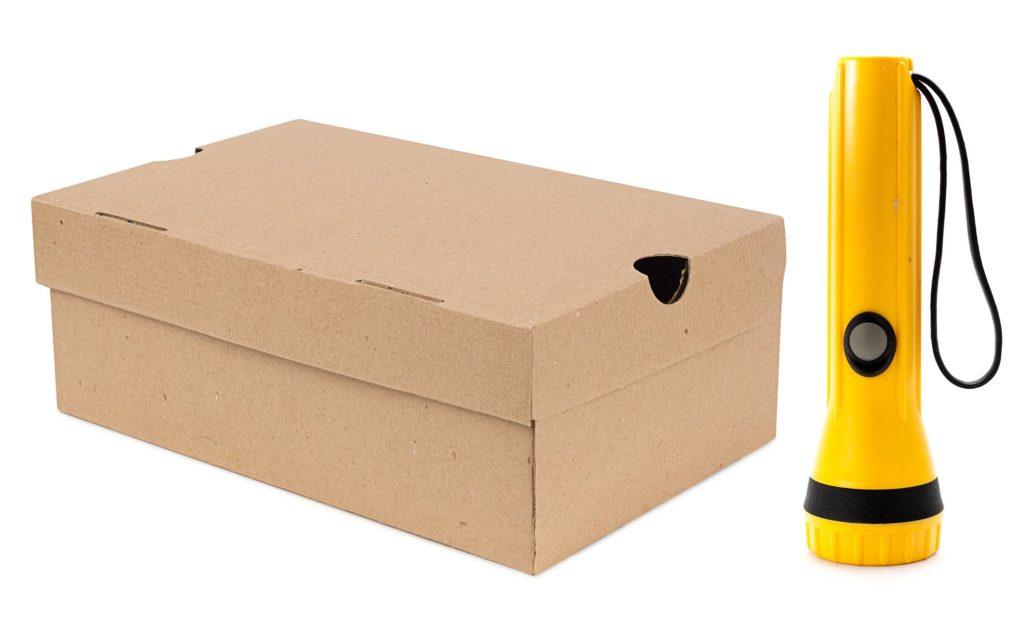 Una caja de zapatos y una antorcha contra el fondo blanco.