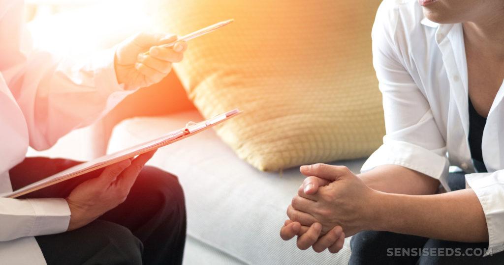 Un médico sosteniendo un portapapeles y un bolígrafo hablando con un paciente sentado en un sofá