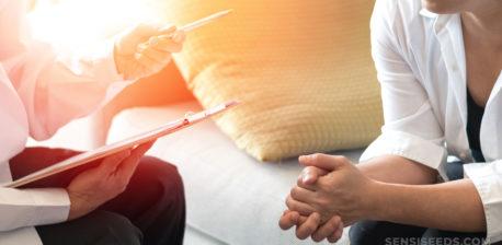 Un médecin tenant un presse-papiers et un stylo parlant à un patient assis sur un canapé