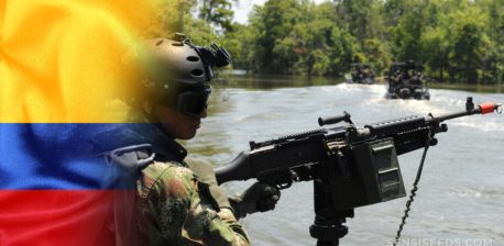 The Colombian flag and a person in military uniform holding a machine gun