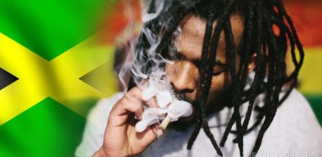 La bandera jamaicana y un hombre con dreadlocks fumando una articulación.