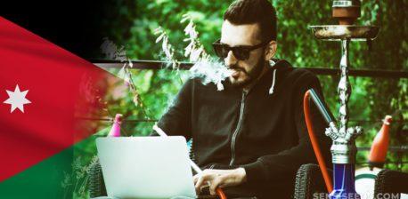 The Jordan flag and a man using a laptop and smoking a shisha pipe