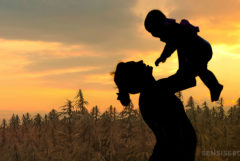 The silhouette of a woman holding up her baby and a field of cannabis plants
