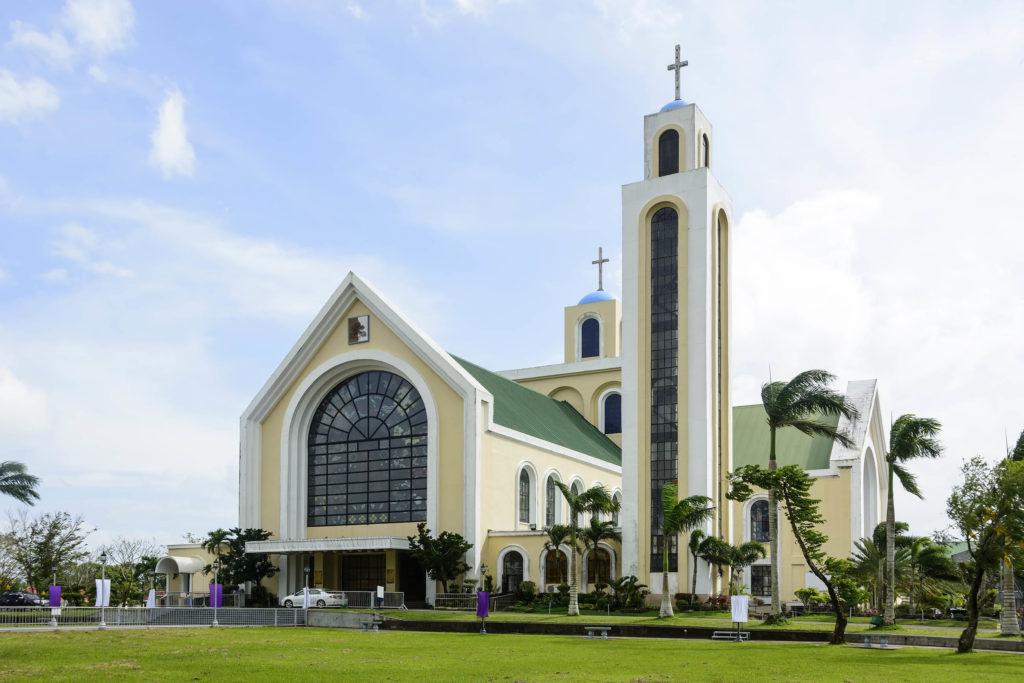 Ein gelbes und grünes Kirchengebäude mit Palmen, die es umgeben