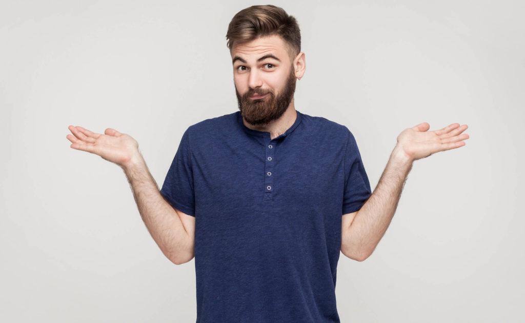 Ein Mann in einem blauen T-Shirt, das seine Hände heraus hält und seine Schultern zuckt