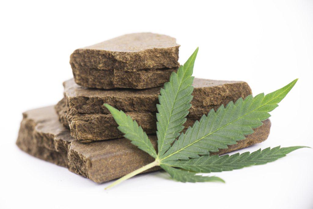 Diferentes tamaños de bloques de hash y una hoja de cannabis.