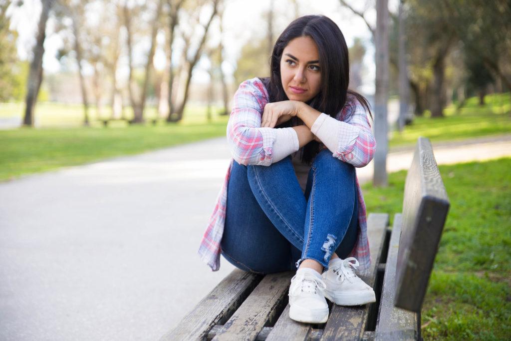 Une femme assise sur un banc de parc étreignant ses genoux à sa poitrine
