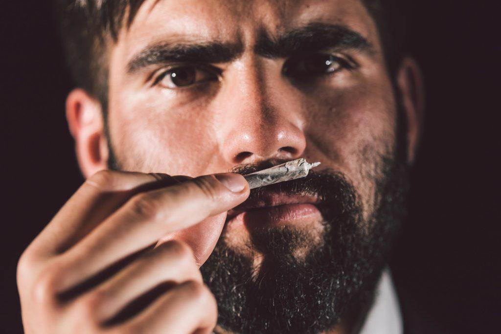 Ein Mann mit einem Bart, der ein gerolltes Gelenk bis zur Nase hält