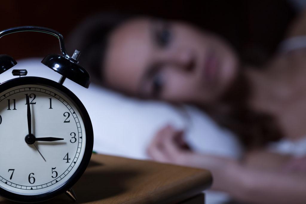 Una mujer acostada en la cama mirando su reloj despertador.