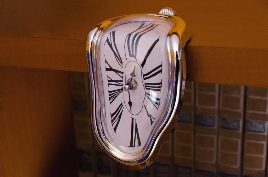 A flat clock that is melting on a shelf