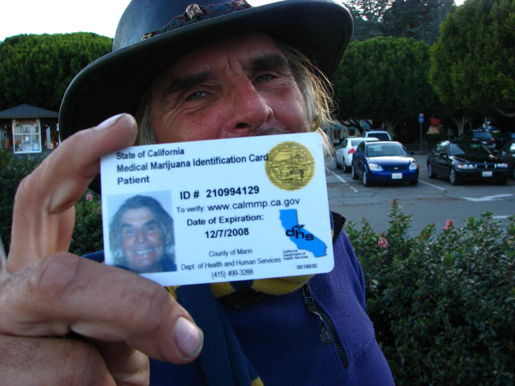 Un homme portant un chapeau tenant sa carte d'identification médicale de marijuana