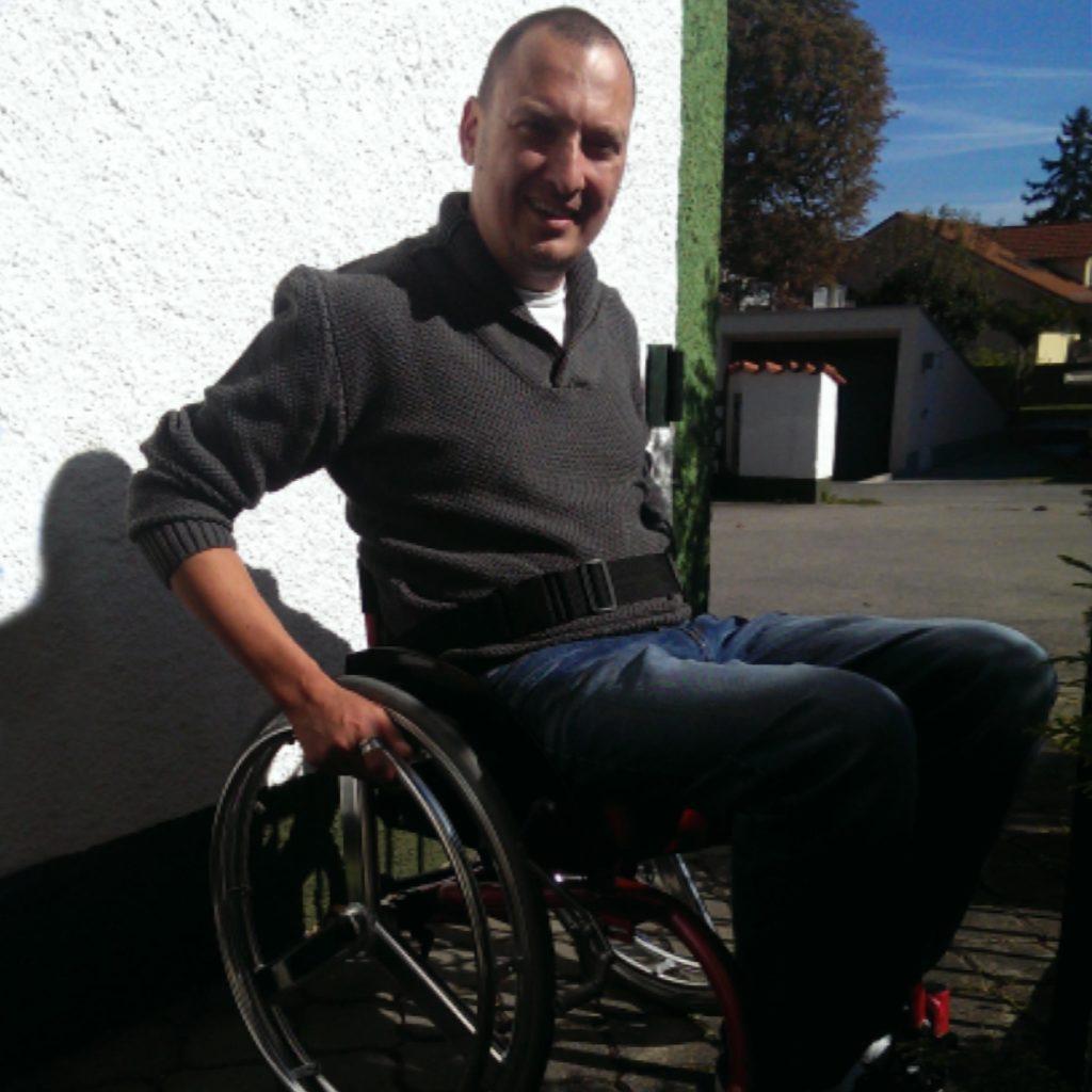 Michael Autrum dans un fauteuil roulant à l'extérieur