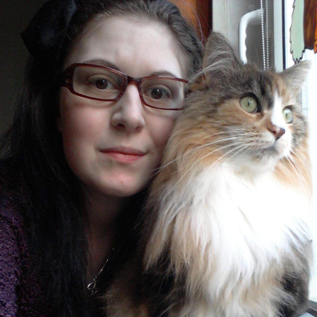 Peggy S. portant des lunettes avec un chat à côté d'elle