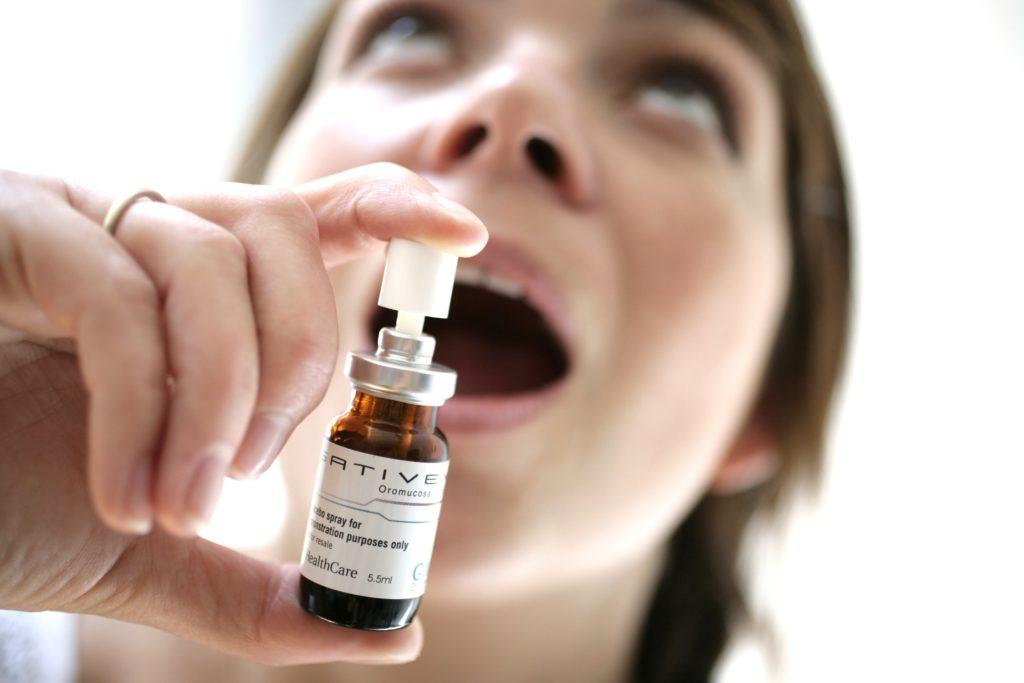 Eine kleine Sprühflasche von Sativx, die auf den offenen Mund einer Person hingewiesen wird