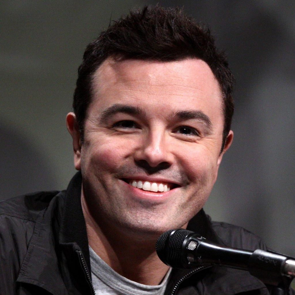 Seth MacFarlane smiling in front of a microphone