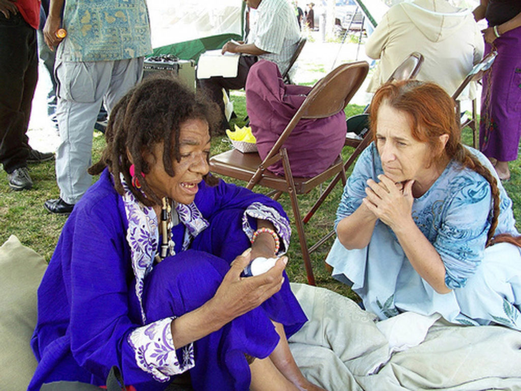 Two women sat talking on the floor of a tent