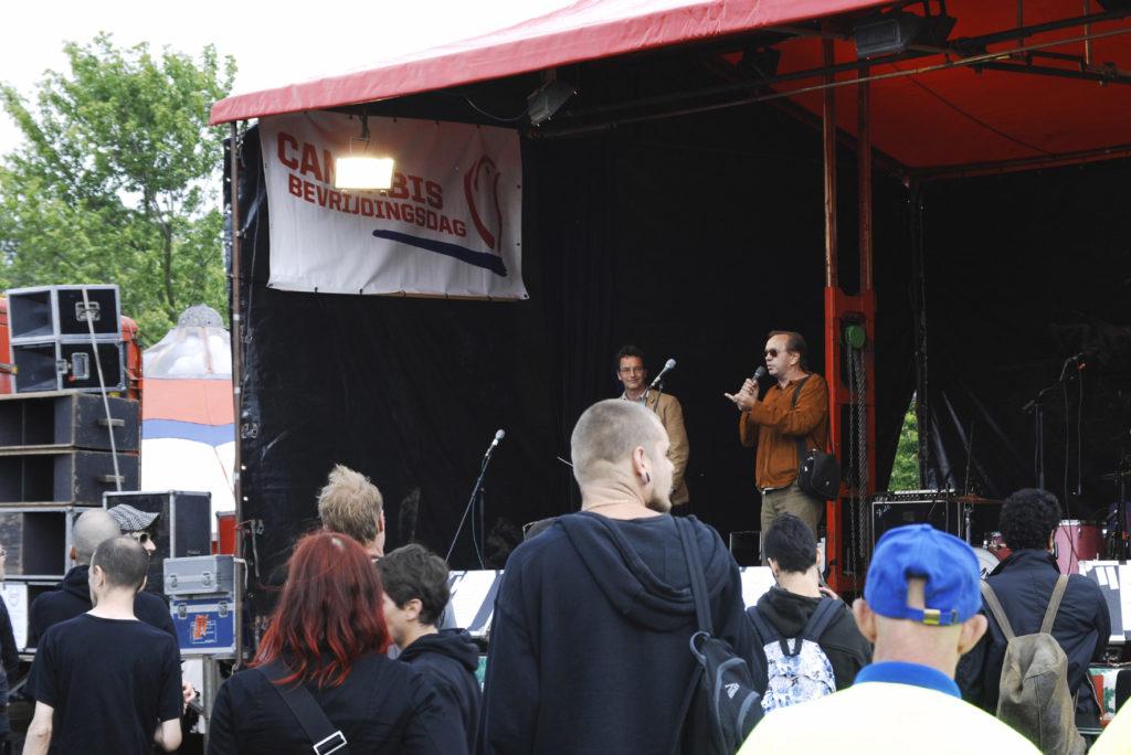 Dos hombres actuando en un escenario al aire libre a una gran multitud.