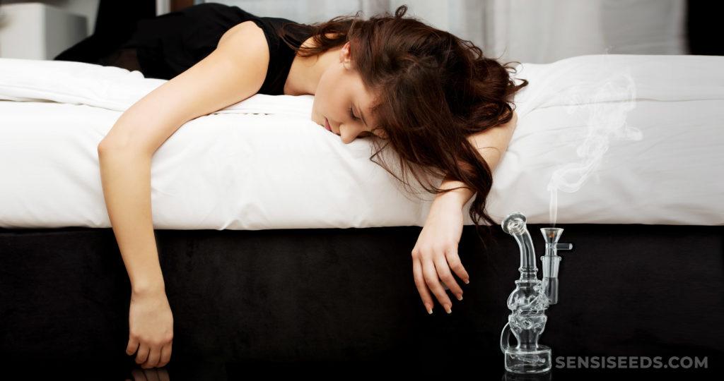 Een vrouw die gezicht op haar bed ligt met haar armen die van de rand hangen