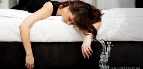 Eine Frau, die nach unten auf ihrem Bett liegt, mit ihren Armen, die vom Rand abhängen