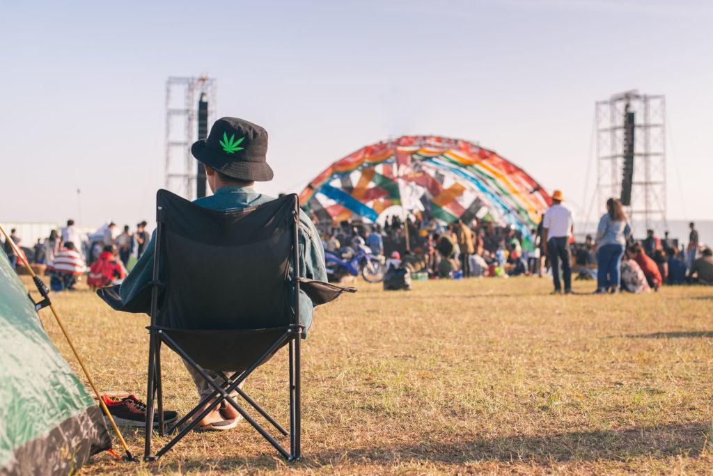 Een persoon die een hoed draagt zat in een kampeerstoel op een festival