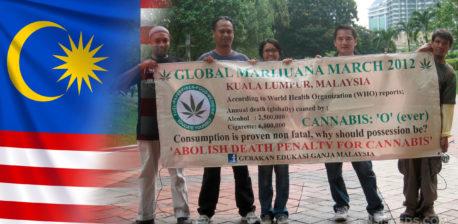 """Die malaysische Flagge und fünf Leute halten ein Zeichen, das ein Zeichen annimmt, dass """"Todesstrafe für Cannabis"""" abspannt """""""