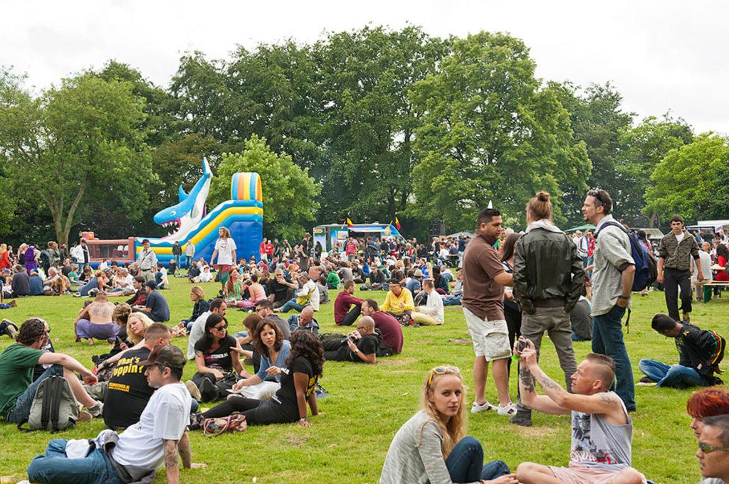 Un campo lleno de personas se sentó en grupos pequeños.