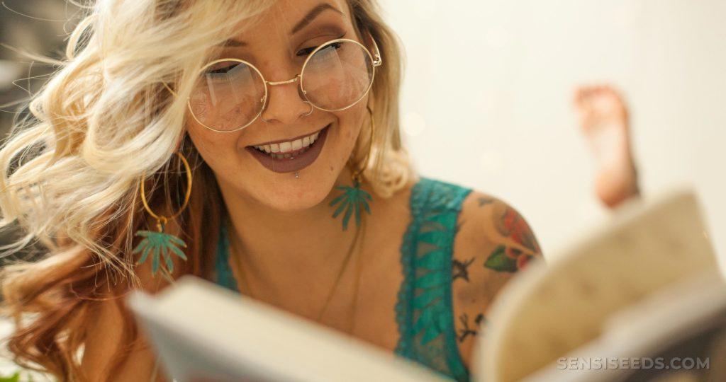 Una mujer con el pelo rubio con oro, gafas redondas leyendo un libro.