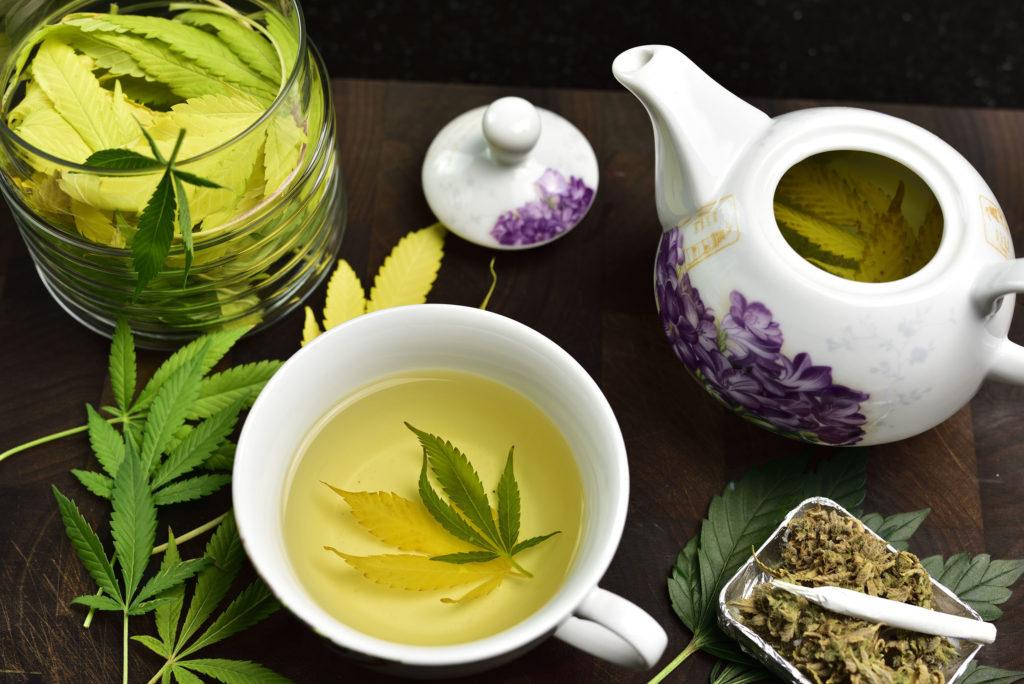 Un plateau de thé blanc et violet et une tasse de thé pleine de feuilles de cannabis