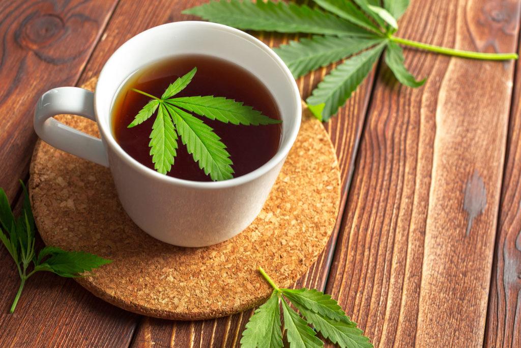 Ein weißer Becher von Cannabis-Tee auf einer Korkuntersetzer