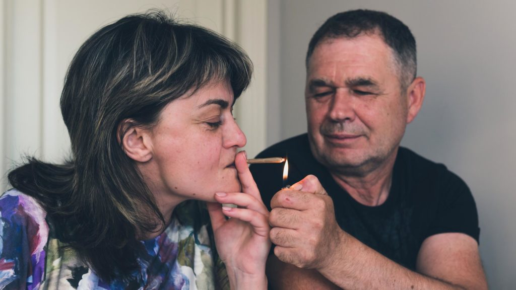 A woman smoking a joint and a man lighting it for her