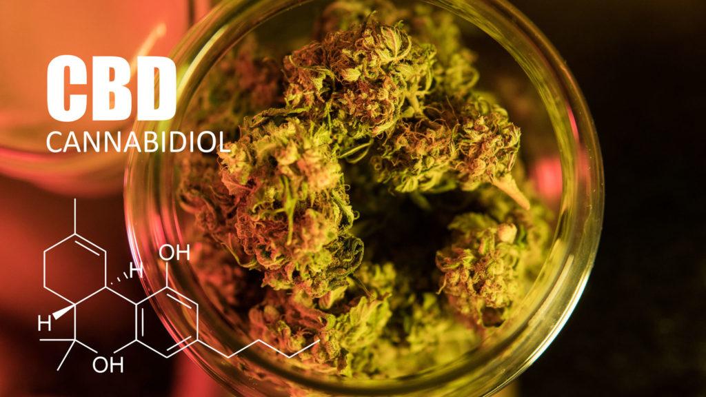 Ein Glasgefäß voller Cannabis-Knospen und der chemischen Formel von CBD