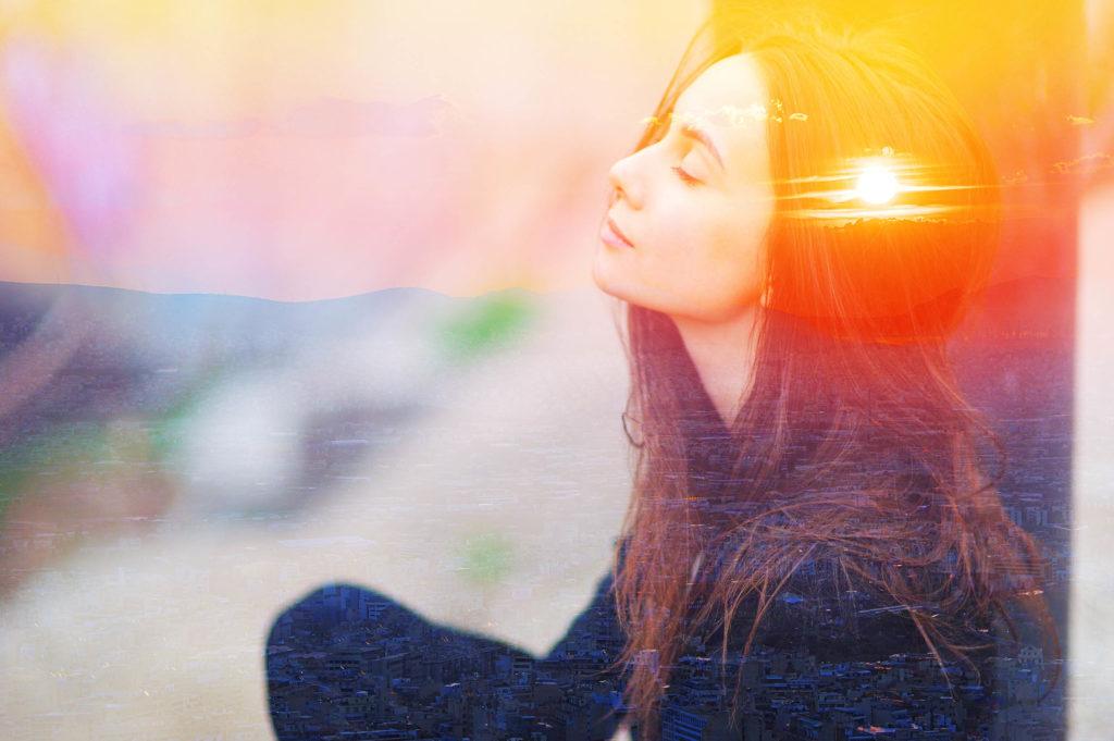 Eine Frau saß mit dem schlossenen Blick kreuzbeinig. Im Hintergrund ist ein Sonnenuntergang