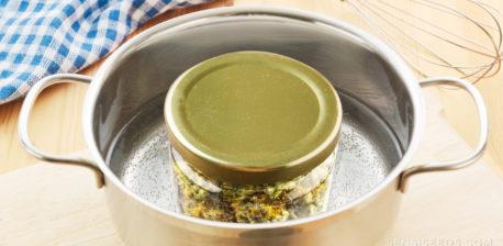 Una olla de cocina con agua hirviendo y un frasco con cannabis.