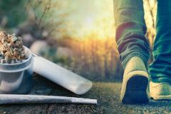 Een persoon die buiten loopt, een molen met cannabisknop, gewricht en lichter