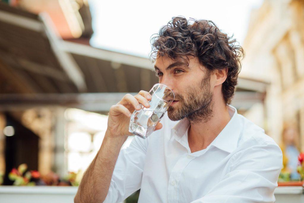 Un homme dans une chemise blanche buvant d'un verre d'eau