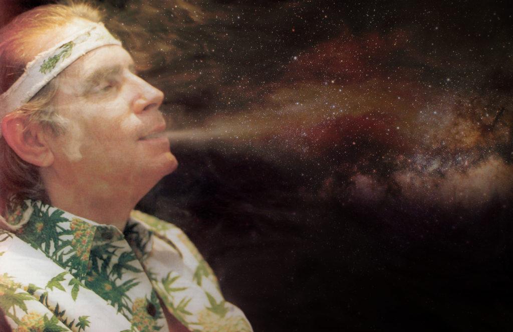 Un homme portant un bandeau blanc et une chemise recouverte de feuilles de cannabis respirant la fumée