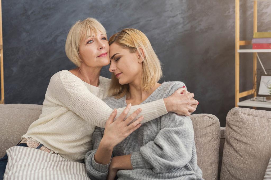 Une femme plus âgée réconfortant une autre femme plus jeune avec ses bras autour d'elle