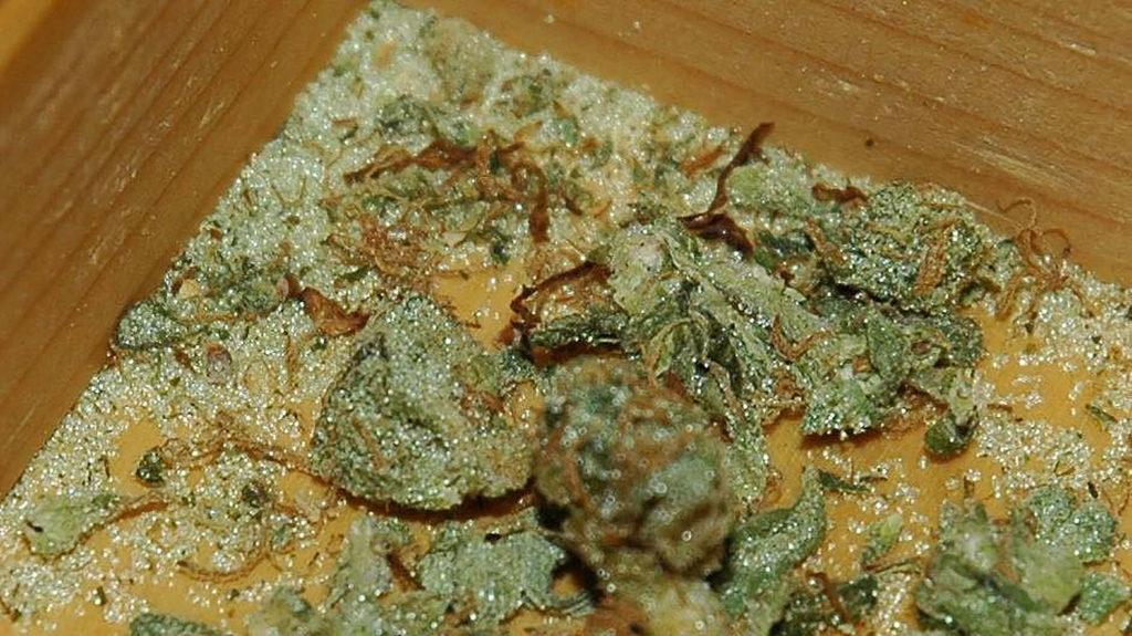 Cannabis à base de plantes dans une boîte en bois avec des éclats de verre saupoudrés partout