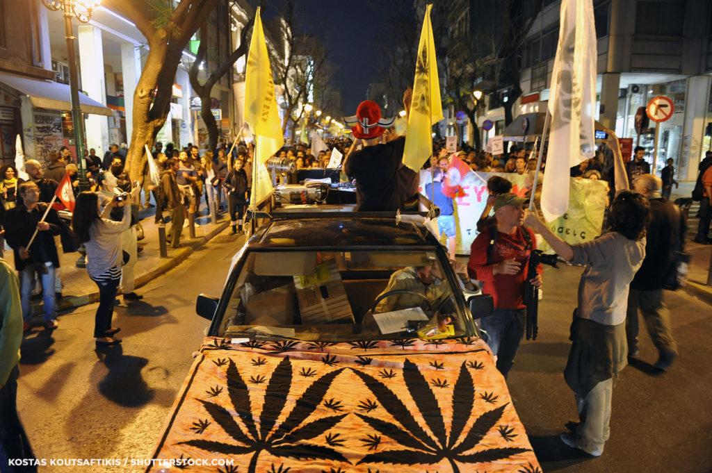 Een auto rijdt door massa's mensen met vlaggen en cannabis-symbolen op de motorkap