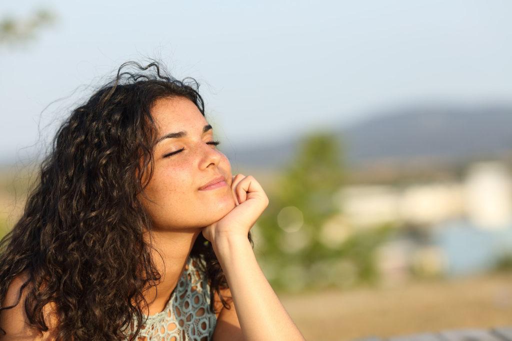 Eine Frau, die mit geschlossenen Augen lächelt und ihr Kinn auf ihre Hand stillsteht
