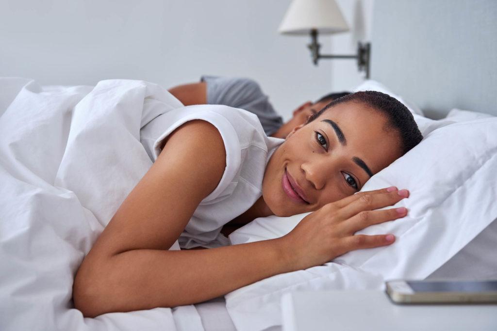 Eine Frau, die im Bett liegend und lächelt
